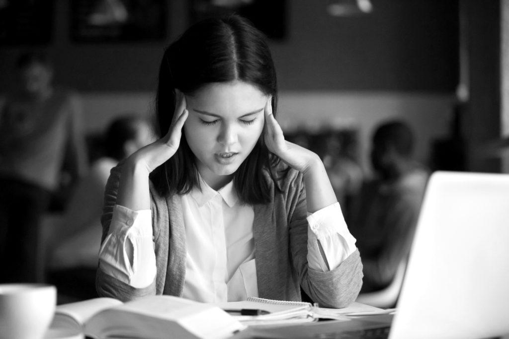 Gestresster Student mit Kopfschmerzen bei der Vorbereitung auf die Prüfung im Cafe