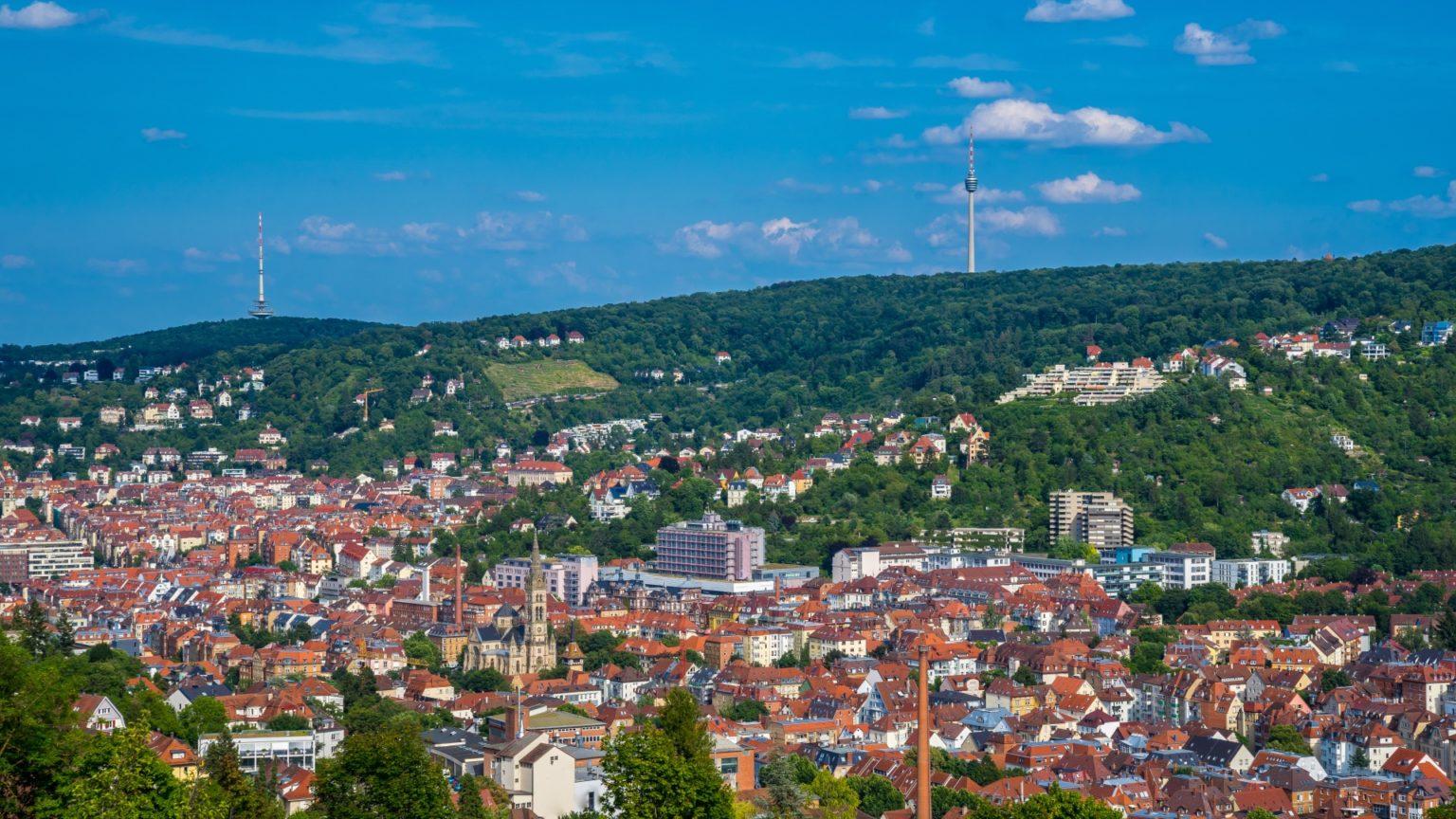 Deutschland, Stadtbild der Stuttgarter Stadtsilhouette von oben im Tal und Fernsehturm auf bewaldetem Berg
